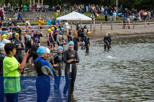 Swimmers wait on the shore of Blue Lake for their wave to start.
